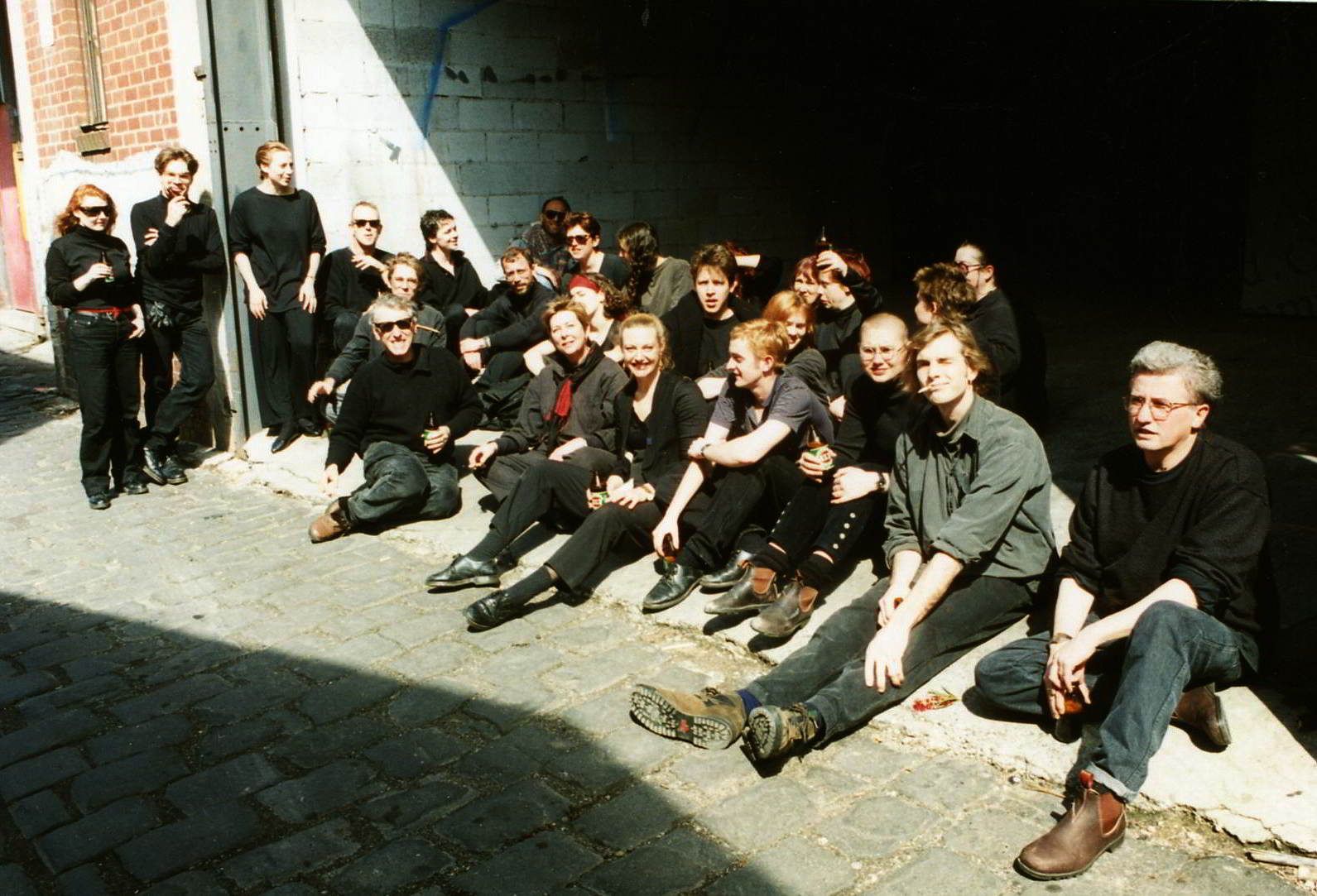 group portrait of performers sitting in a cobbled laneway