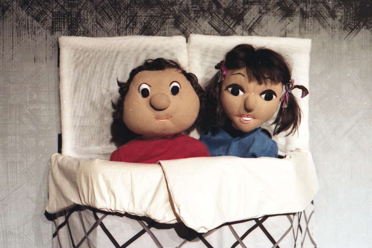 Colour picture of boy and girl puppet in bed