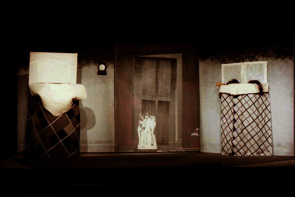 bedroom setting on stage two beds and outline of a tiger visible through central door
