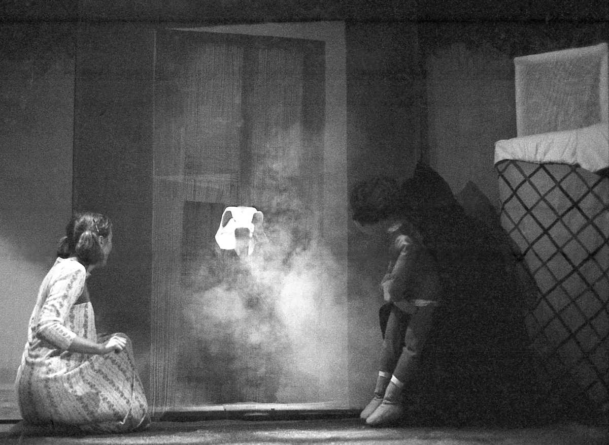 Jandy Malone and the Nine O'Clock Tiger Handspan Theatre - a girl kneeling on floor with puppet looking at a shadowy tiger figure through the doorway