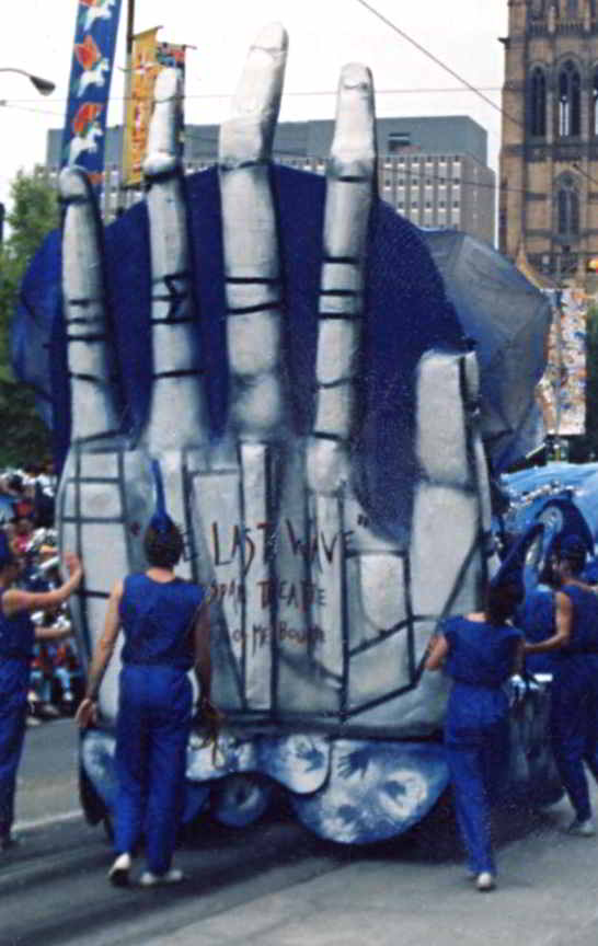 large white hand with words the last wave being pushed along the street by people in blue overalls
