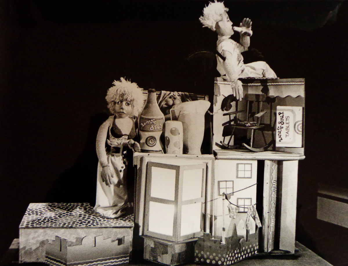 man and woman puppet in a cardboard model house