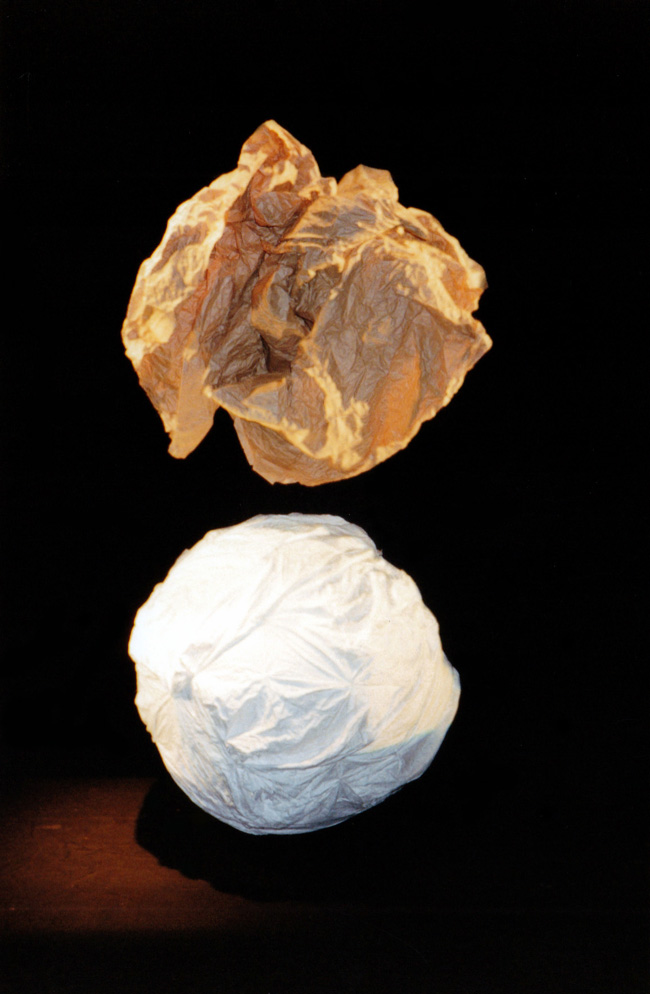 Metafour, Katy Bowman Cycle segment - a scrunched ball of brown paper hovering over white cloth ball against black background