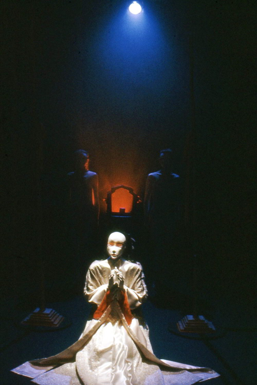 white robed figure holding a white face mask kneeling  under a blue spotlight in front of an upstage red-lit alcove