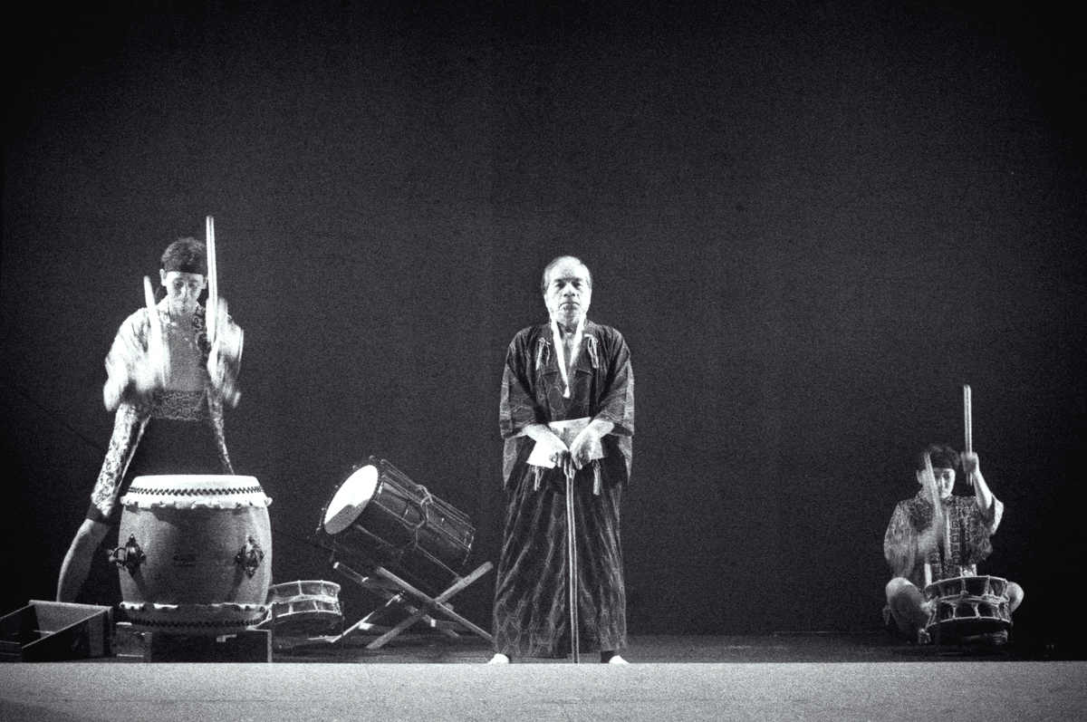 Miss Tanaka Handspan/Playbox One man stands centre-stage with taiko drummers to left and right of him