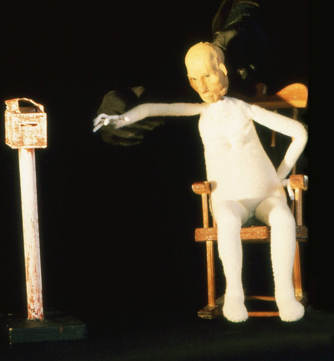 Puppet figure of old woman stretching from rocking chair to letter box