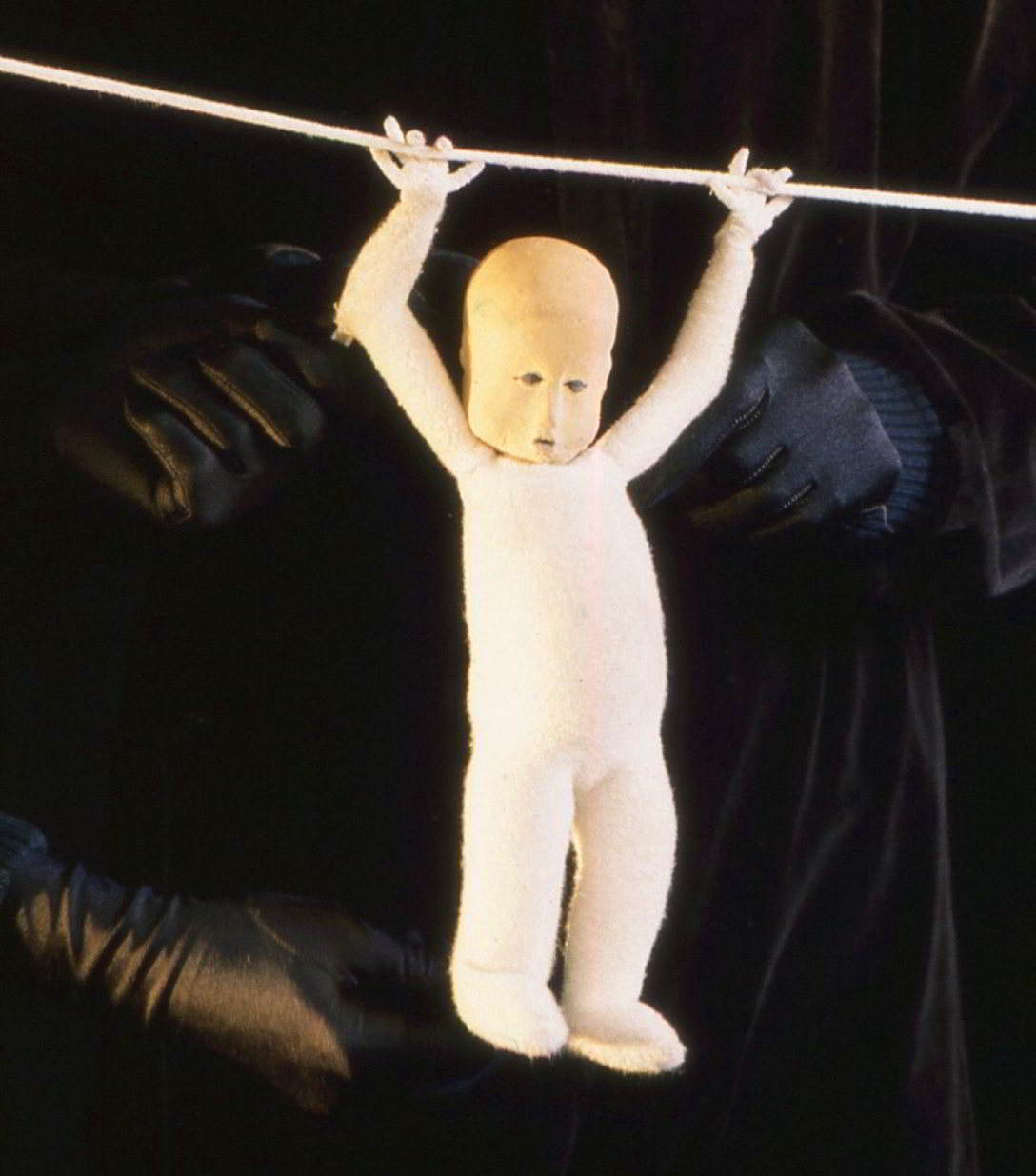 Handspan Theatre Moments a puppet figure hanging by arms swinging on a wire