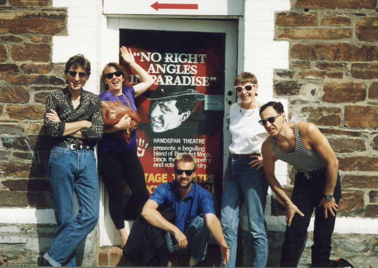 5 people with sunglasses around show poster in doorway of stone wall