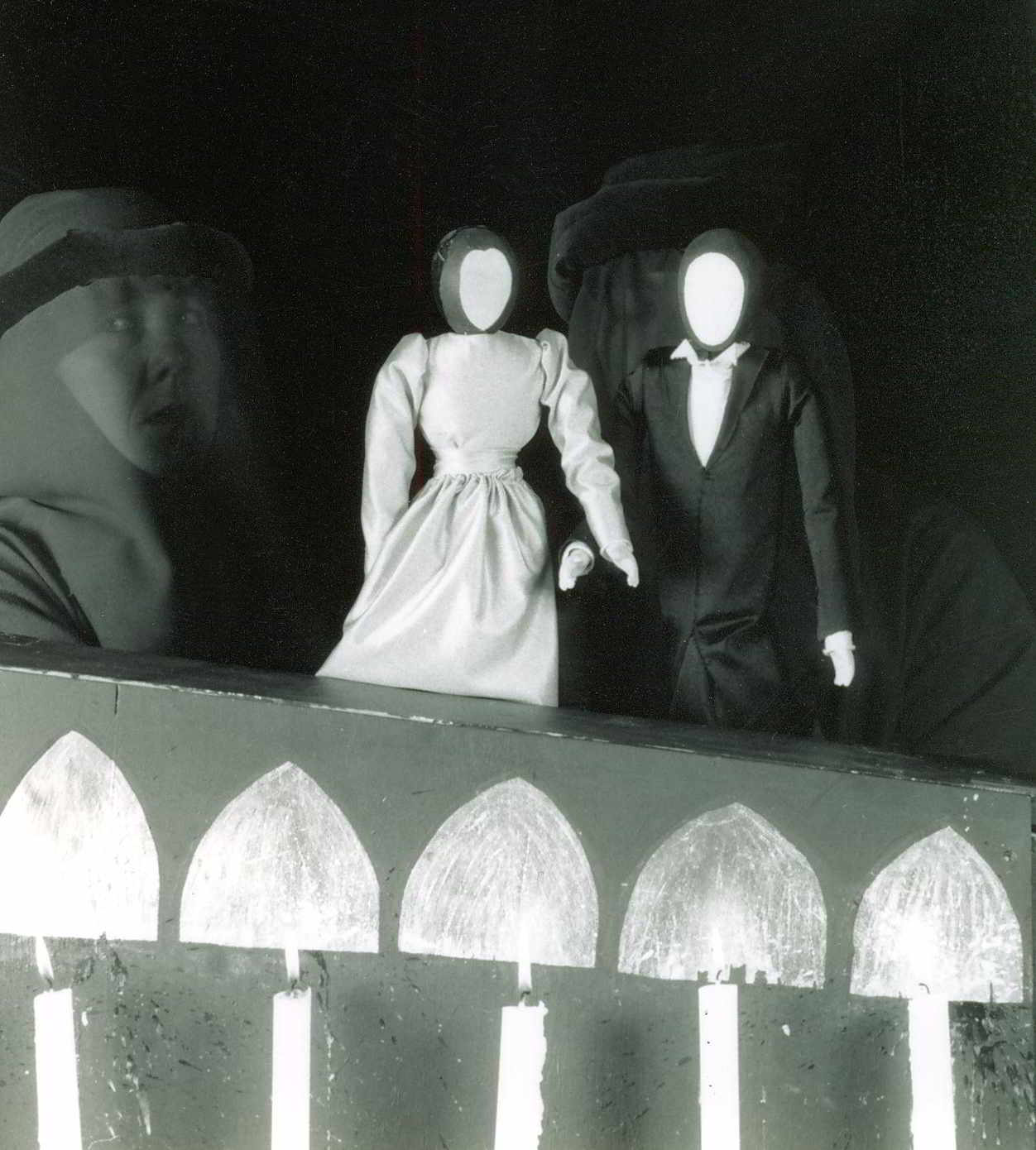 blank-faced man and woman puppets with hooded puppeteer