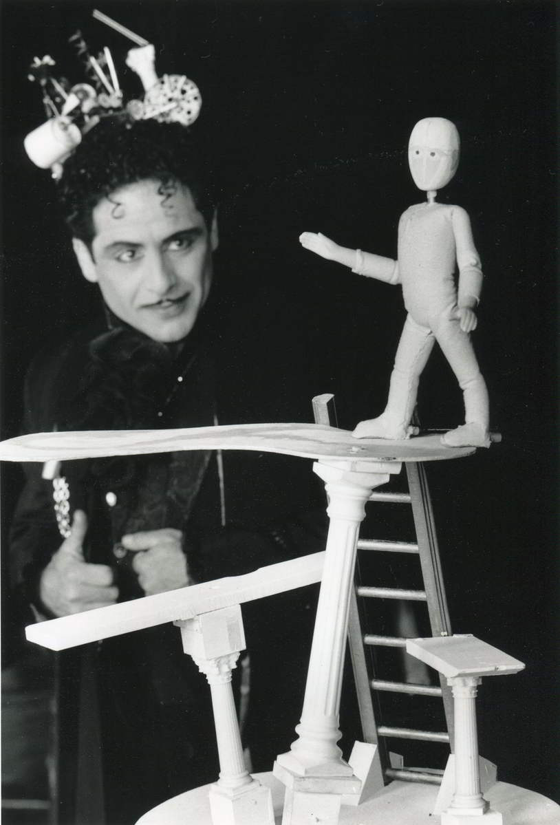 No Right Angles in Paradise Magician Sam Angelico watching a puppet balance on miniature diving board