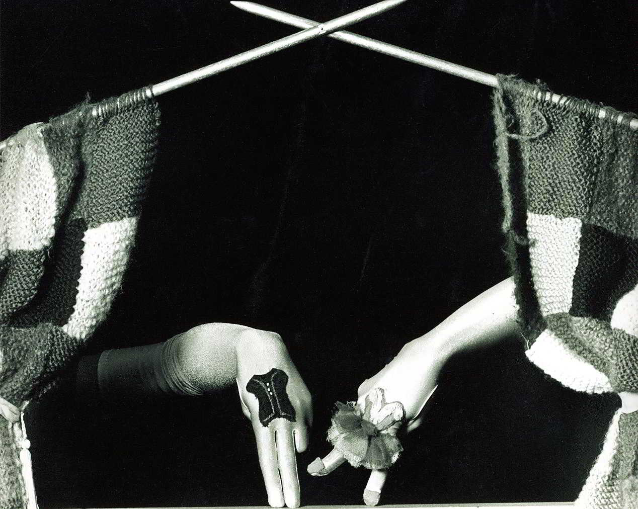 curtain of knitting on needles with dressed fingers dancing