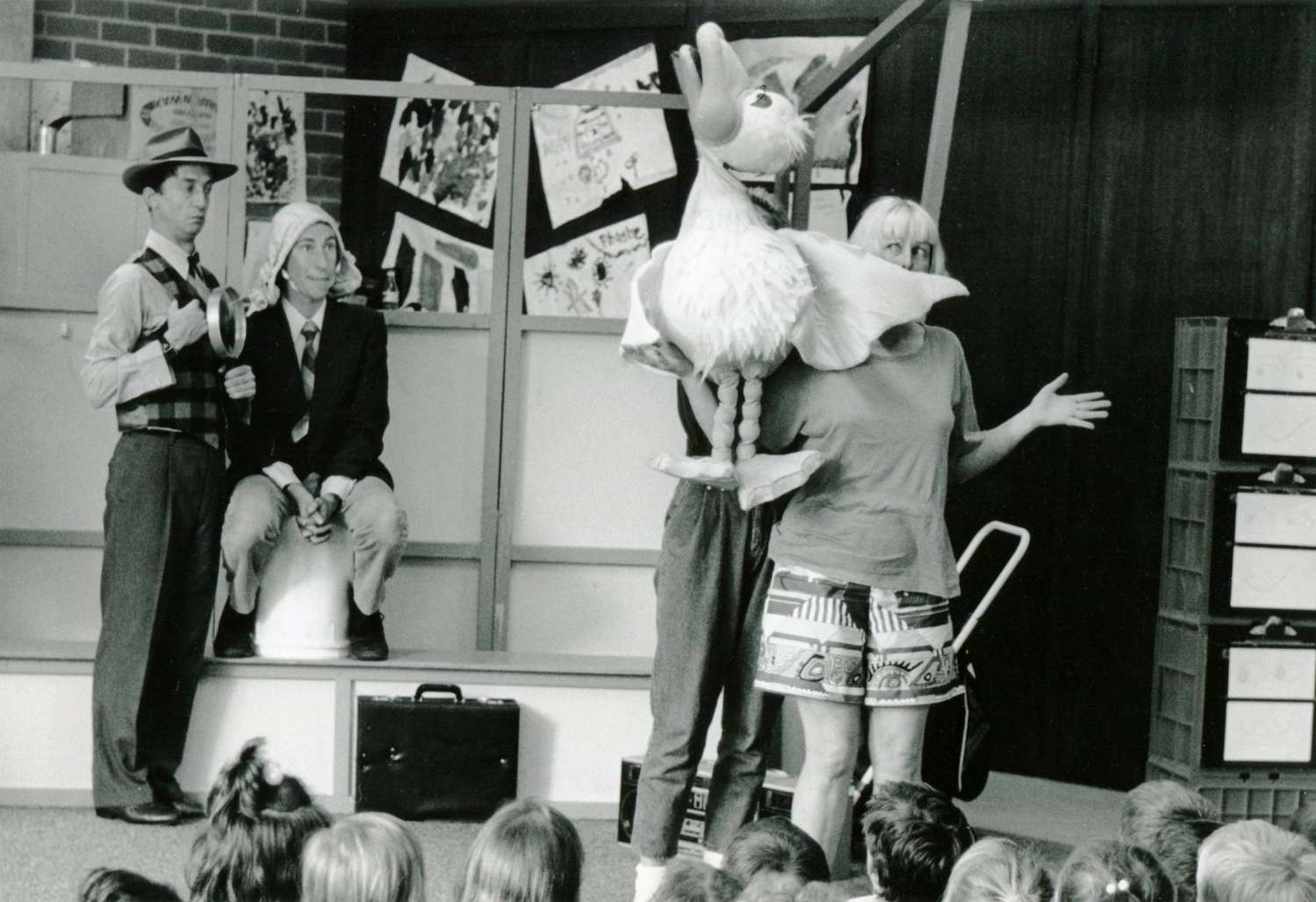 actors on stage in a classroom with puppet duck, head held high, quacking