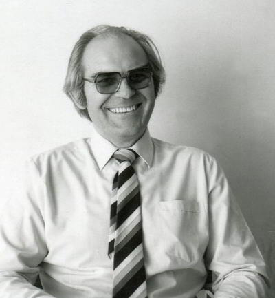 portrait of seated, smiling man in business shirt and striped tie