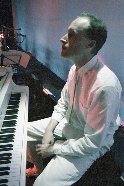 man sitting at a piano with hands in his lap wearing white shirt and trousers backlit in blue and pink lighting