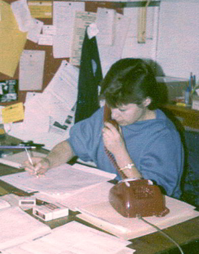 colour picture of young woman with pencil in hand and telephone at her ear seated at a desk covered in papers