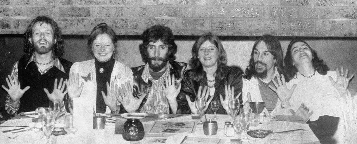 Handspan Theatre six founding members at dinner table with their hands held open in the company logo