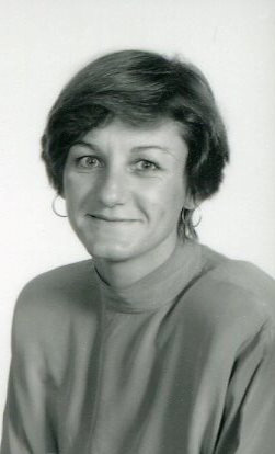 black and white portrait of woman grinning at camera