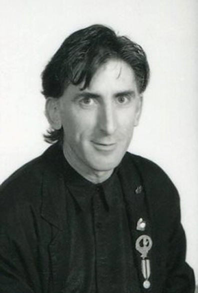 black and white portrait of man with badge on jacket lapel