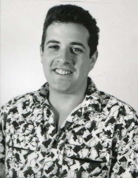 portrait of a young man with dark hair wearing a patterned shirt