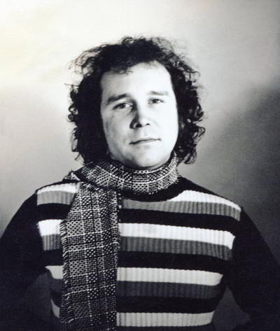 portrait of round-faced man with curley hair wearing striped jumper and scarf