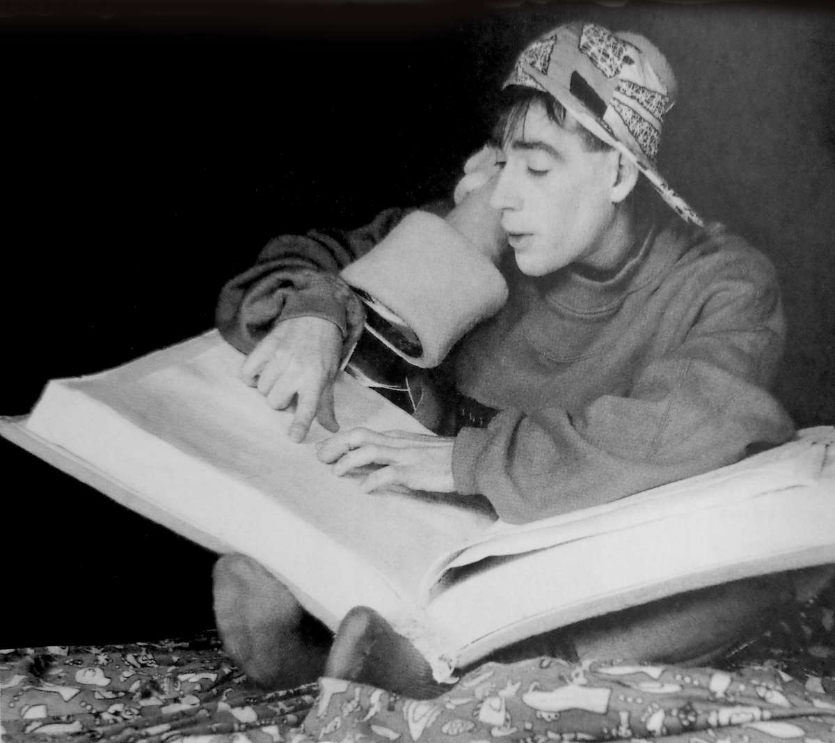 boy in baseball cap reading a very big book