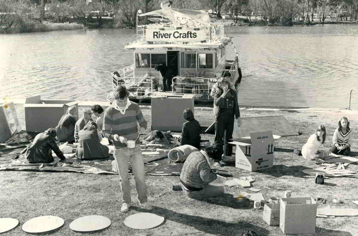 Rivercraft, Mildura John Rogers with craft materials on the bank of a river with houseboat on the water