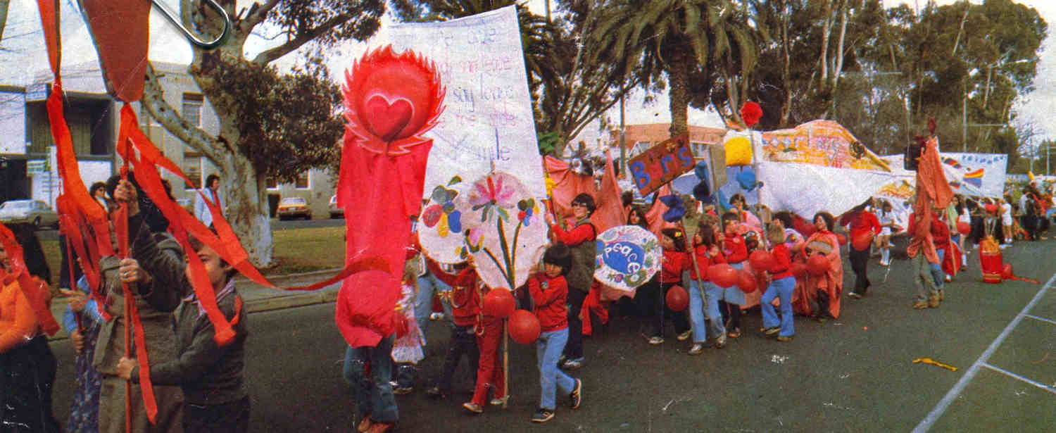 lStreet Parade Mildura street children wearing  red clothing and carrying red parade puppets, objects and signs