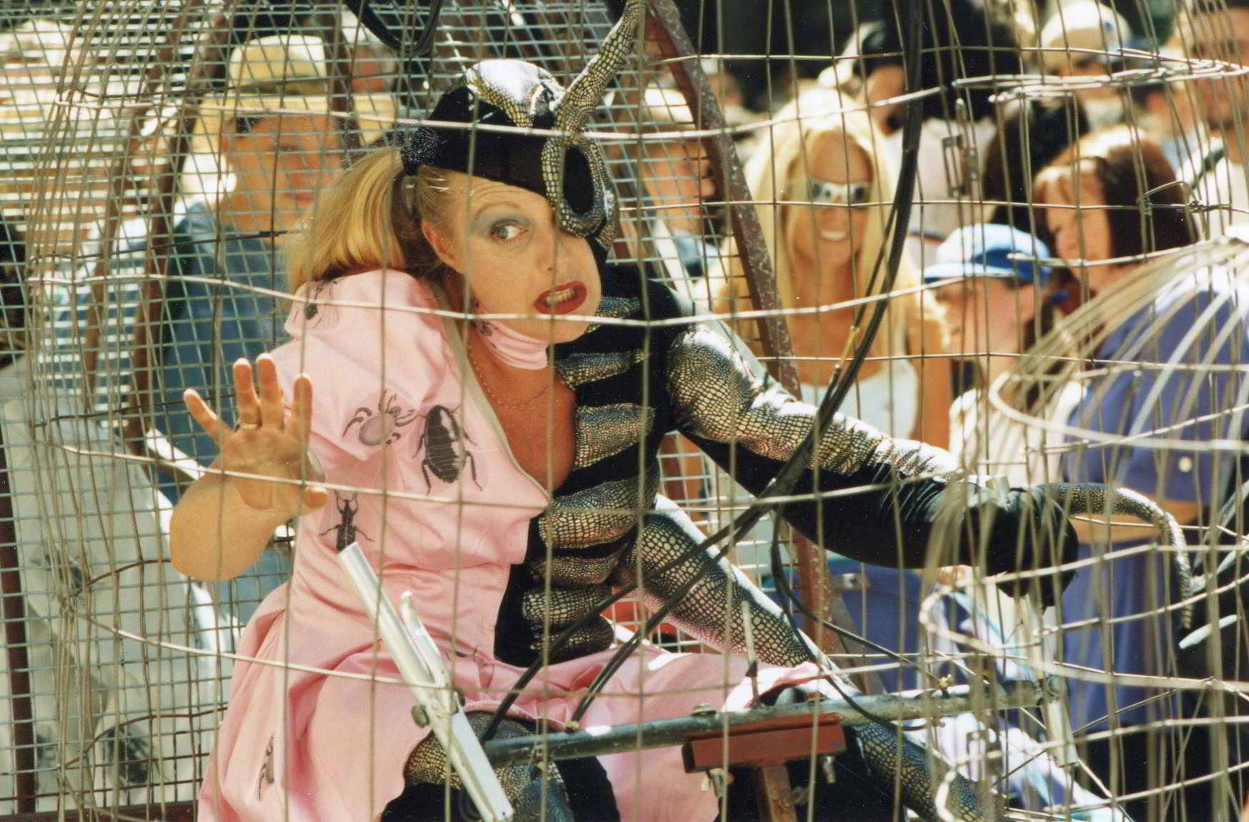 Road Roach strret theatre image a close up actor in dual costume pink dress and black and silver insect, inside a cage