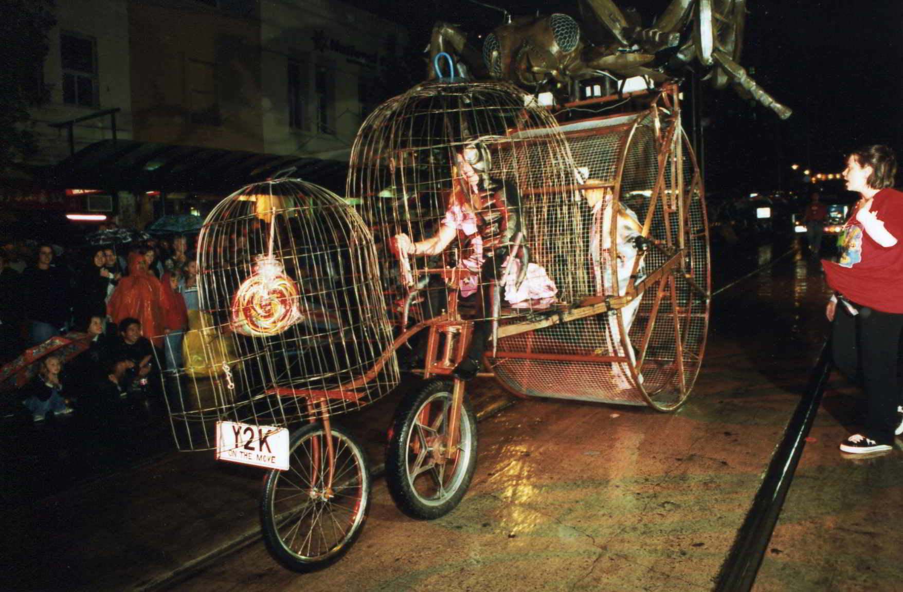 Road Roach's 3 cage parade contraption on the street at night