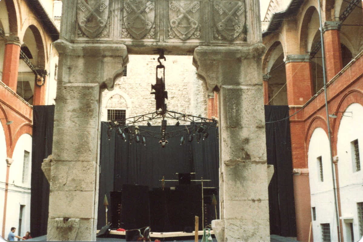 Carved stone arch and beyond it a demountable stage hung with black curtains