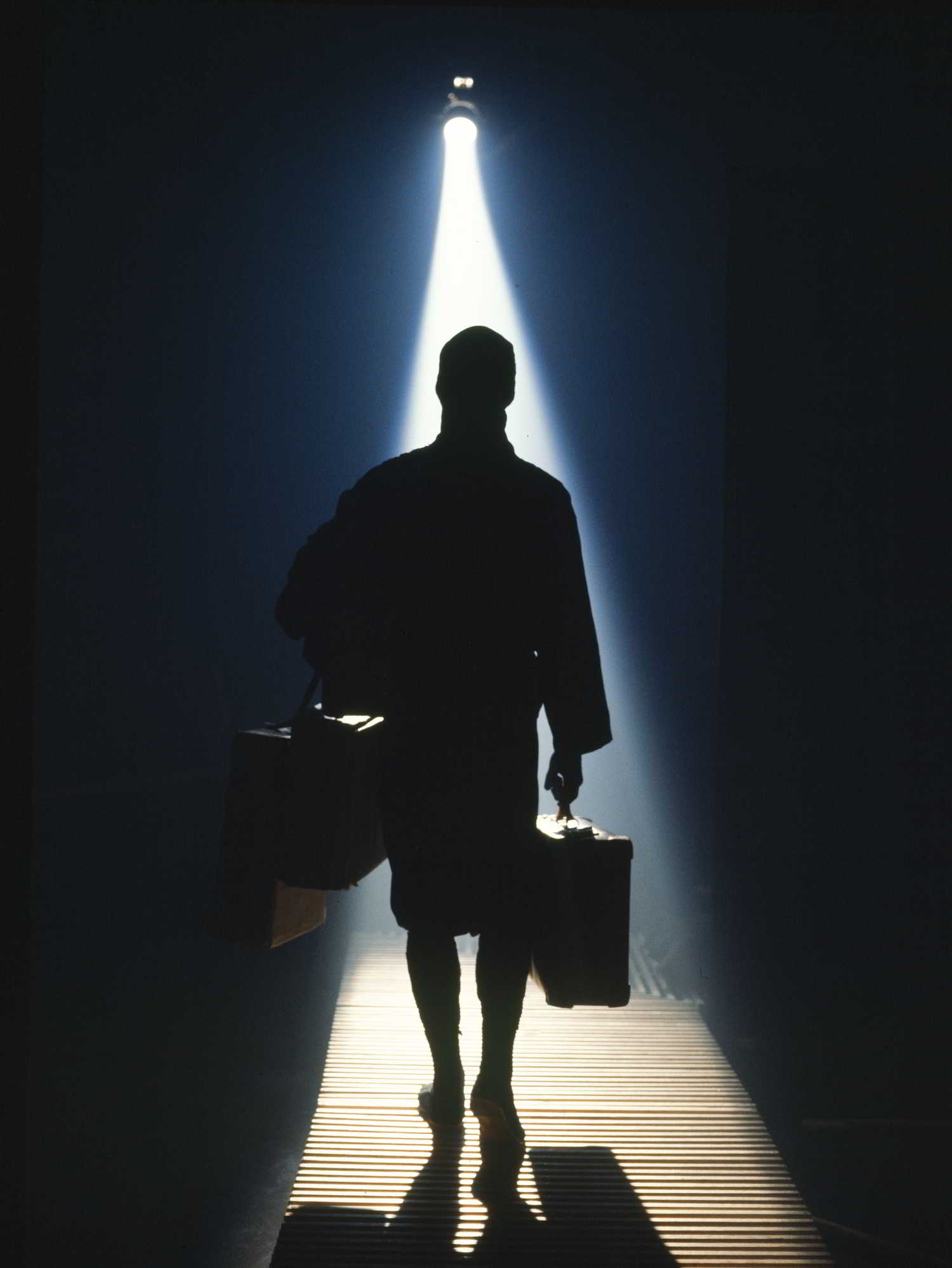 Secrets Handspan Theatre man carrying two suitcases, silhouetted against a shaft of light