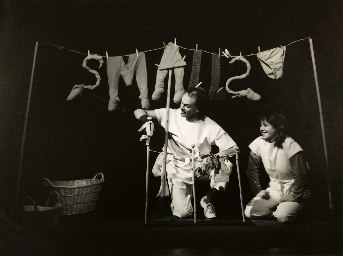 man and woman with miniature clothesline  in from of larger version with hanging articles making the word smalls