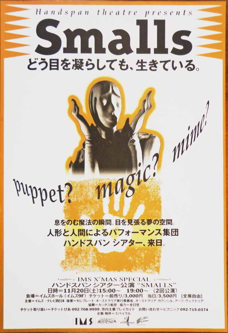 gold black & white poster with text in English & Japanese with central image of puppet head and hands