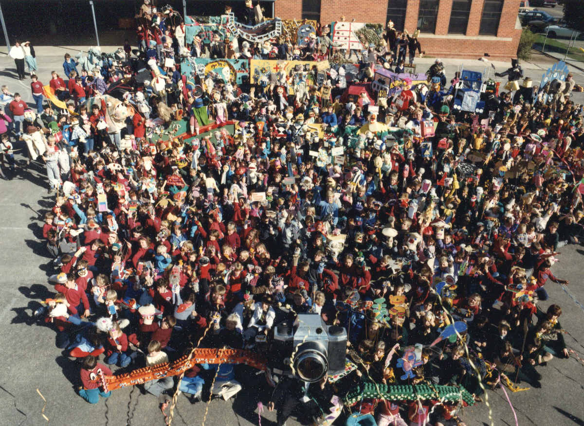 Snapshot artist-in-residency - finale aerial view of massed crowd of children carrying puppets around a large camera