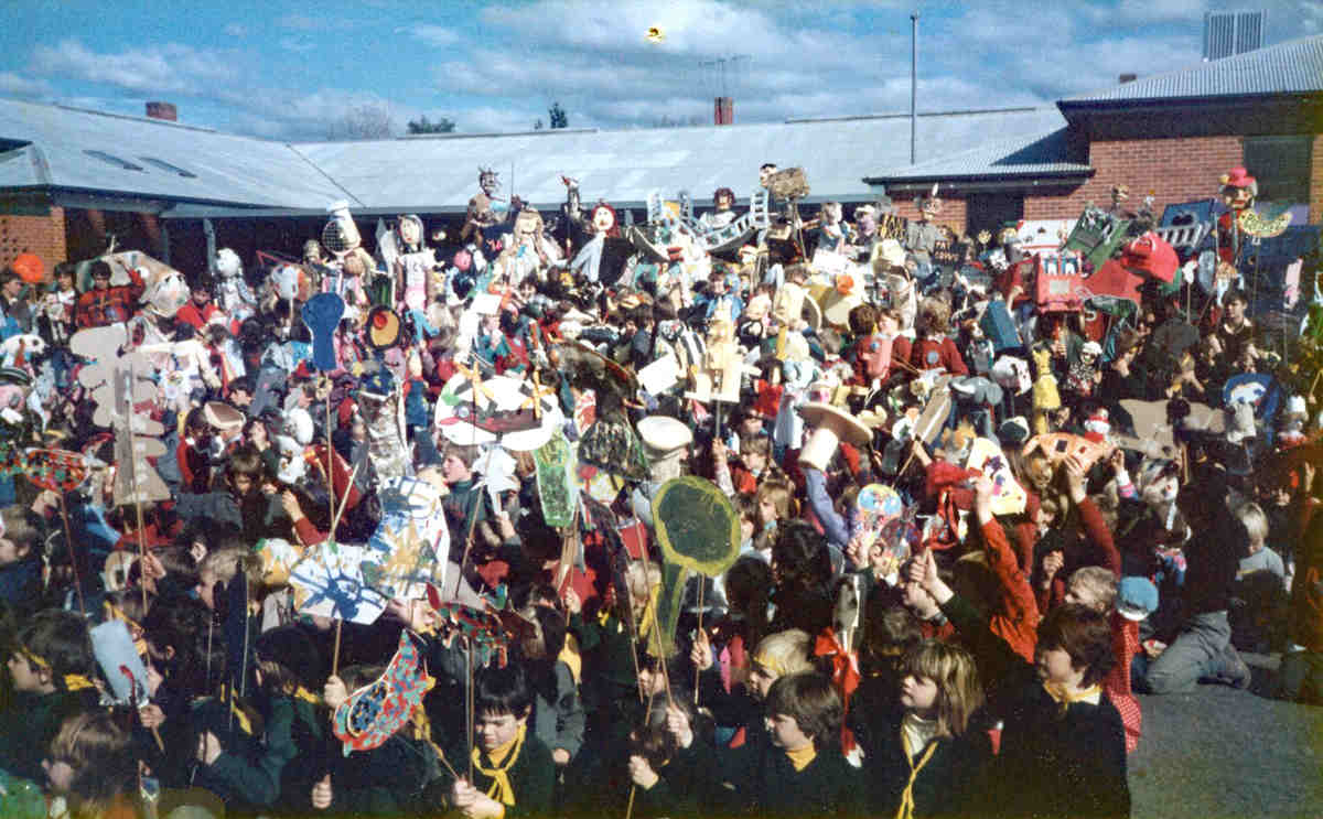 large crowd of children holding puppets