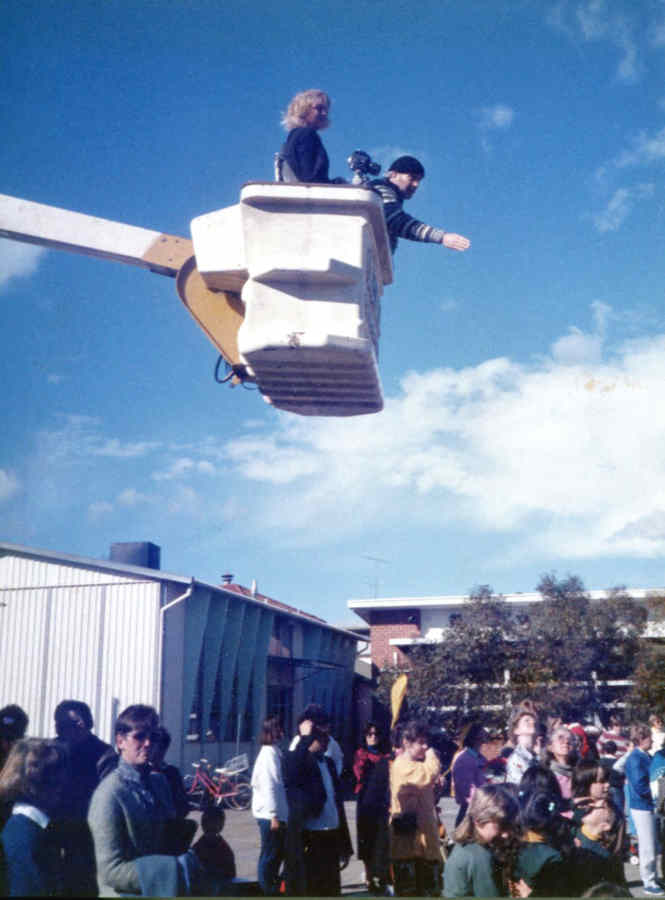 man and woman high above crowded school playground