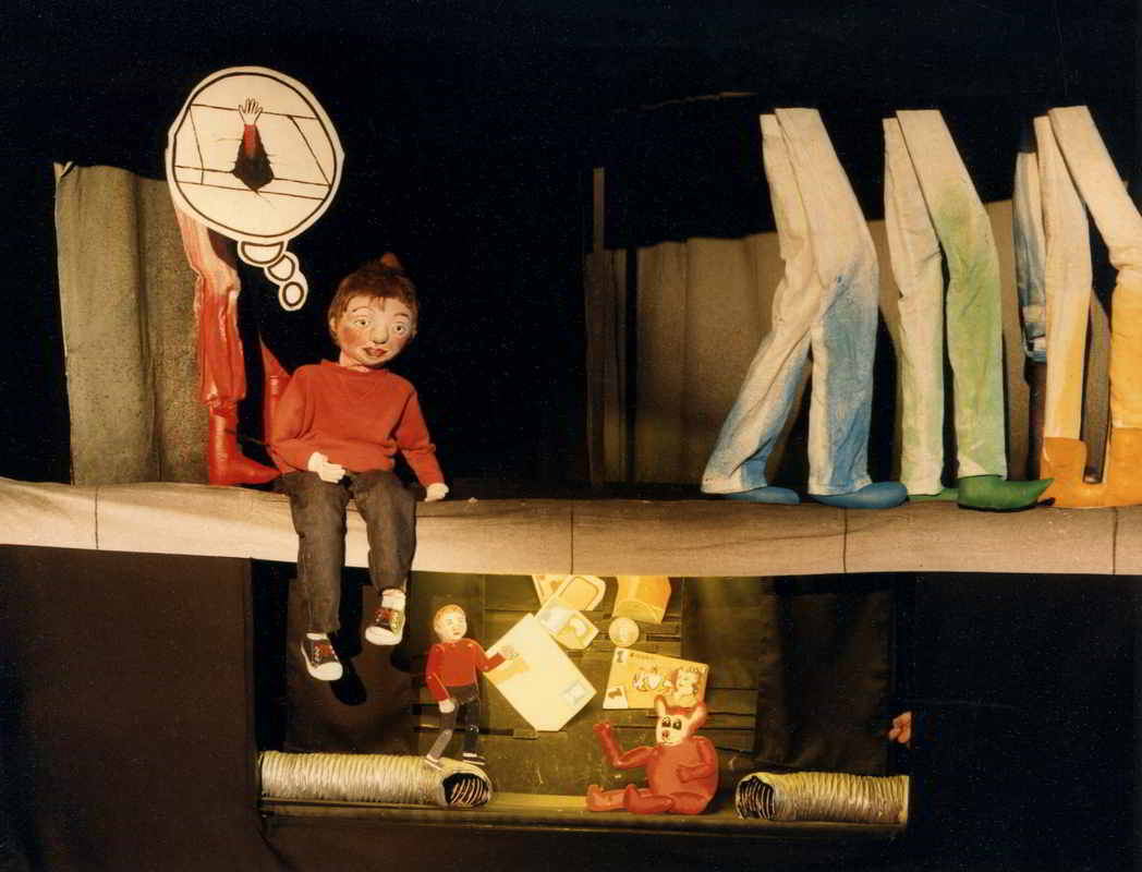 Boy puppet sitting on pavement with legs with toy theatre scene of boy, bear and rubbish below ground