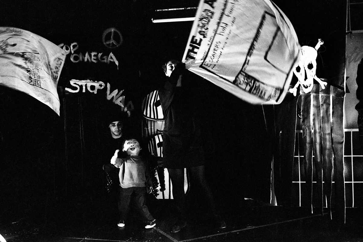 Streetwise Handspan Theatre boy puppet in spooky alleyway with  grafitti and flying newspaper