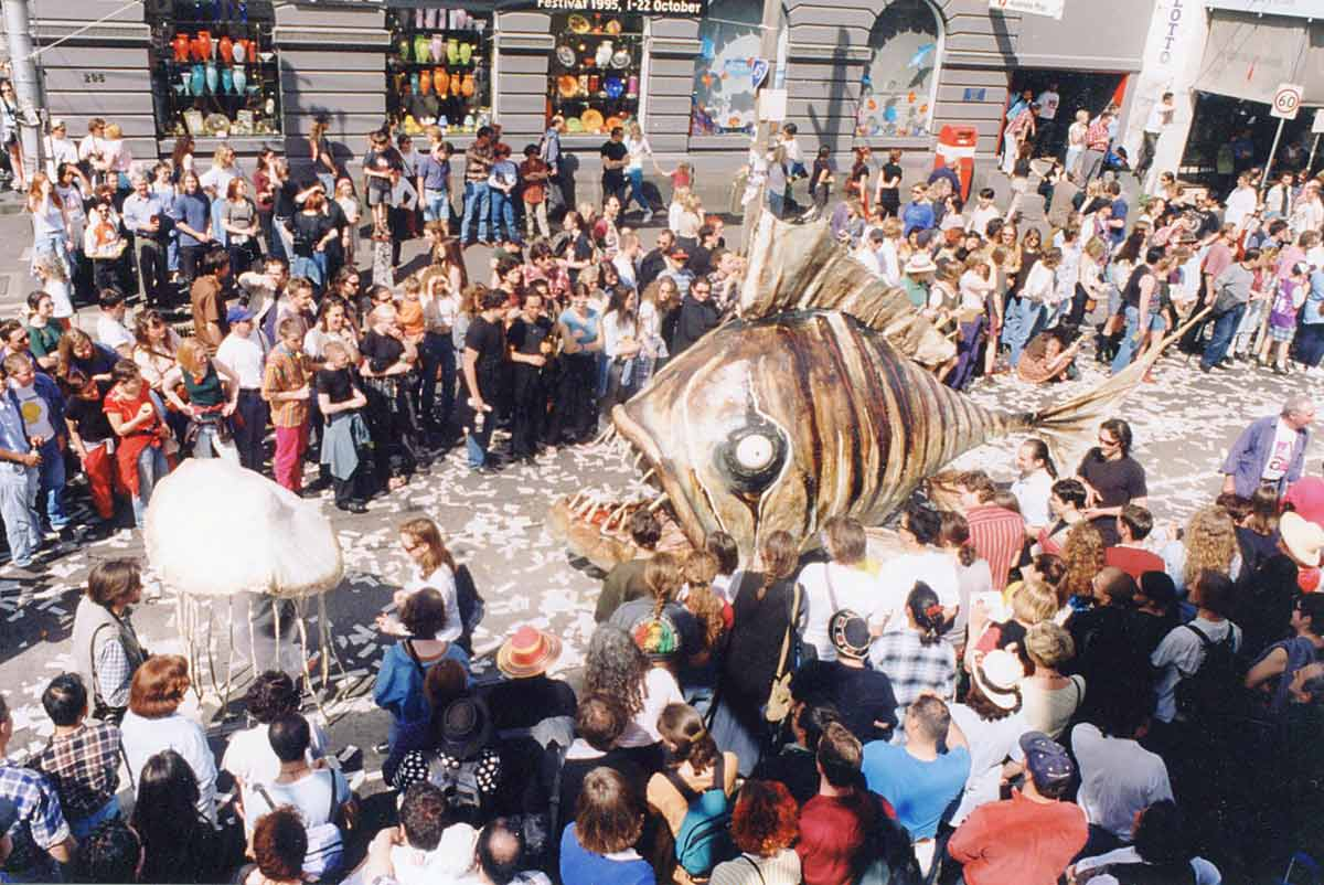 Swim Handspan Theatre large cane fish painted in brown tones following white jelly fish on parade down a crowded city street