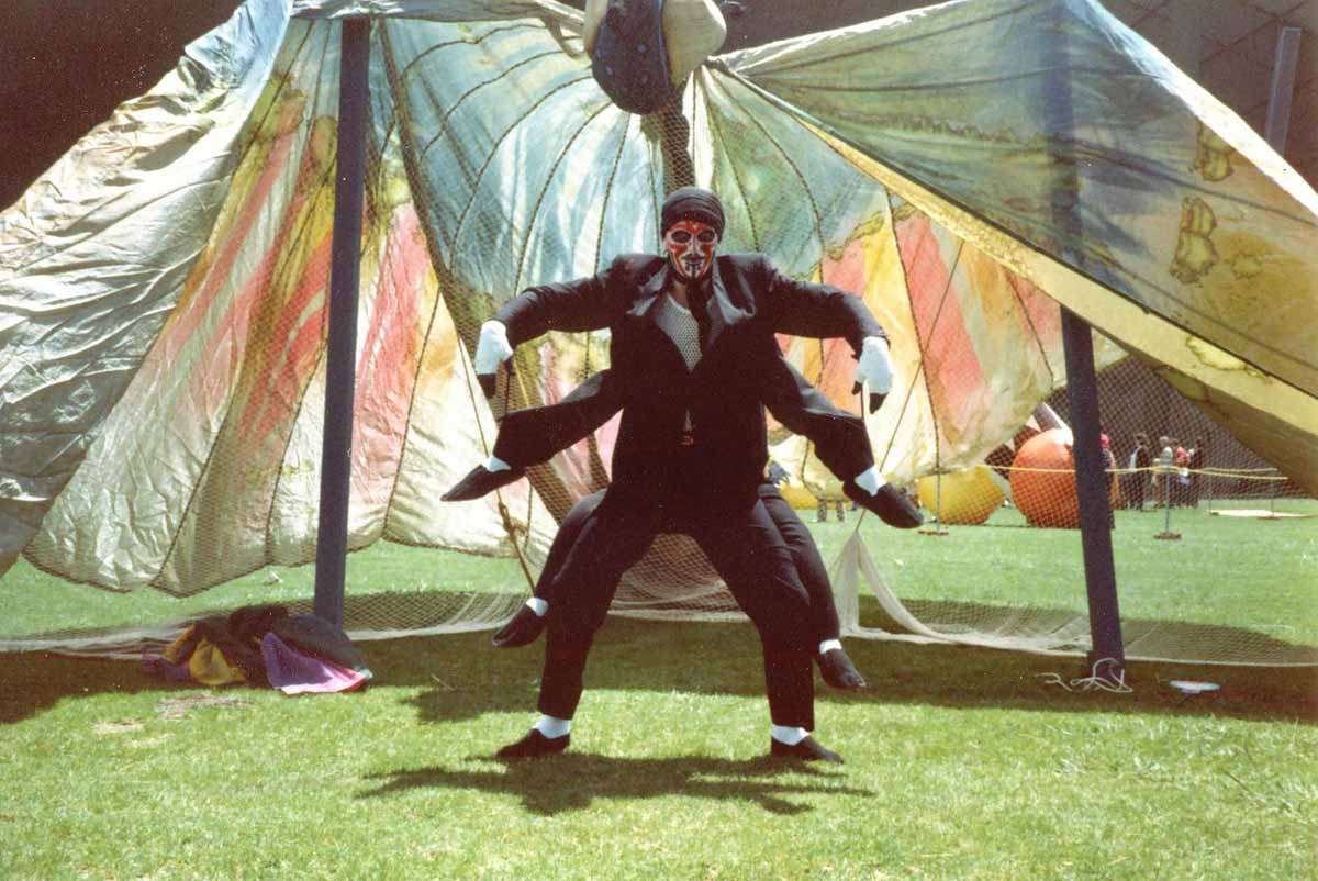 actor dressed in a spider costume in front of butterfly wing backdrop