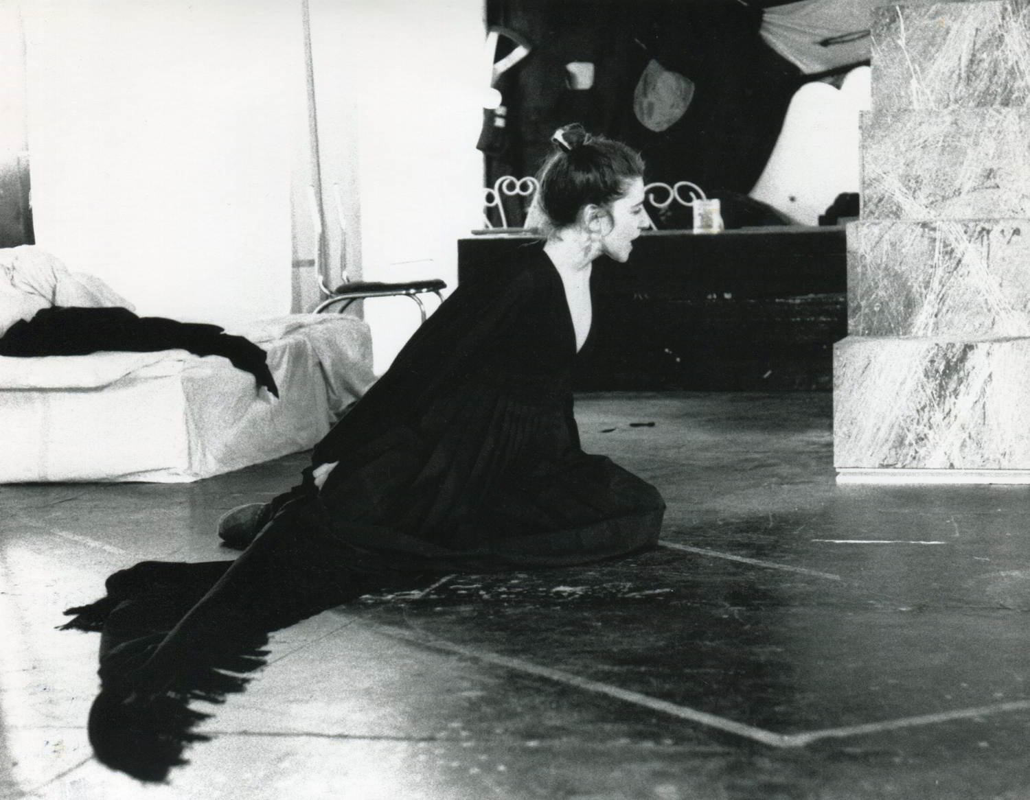 woman in black on floor stretching upwards