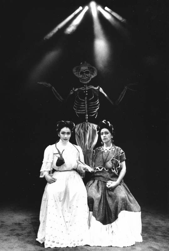 Handspan Theatre Viva La Vida - Frida Kahlo two women in long dresses seated in front of a looming skeleton in light beams