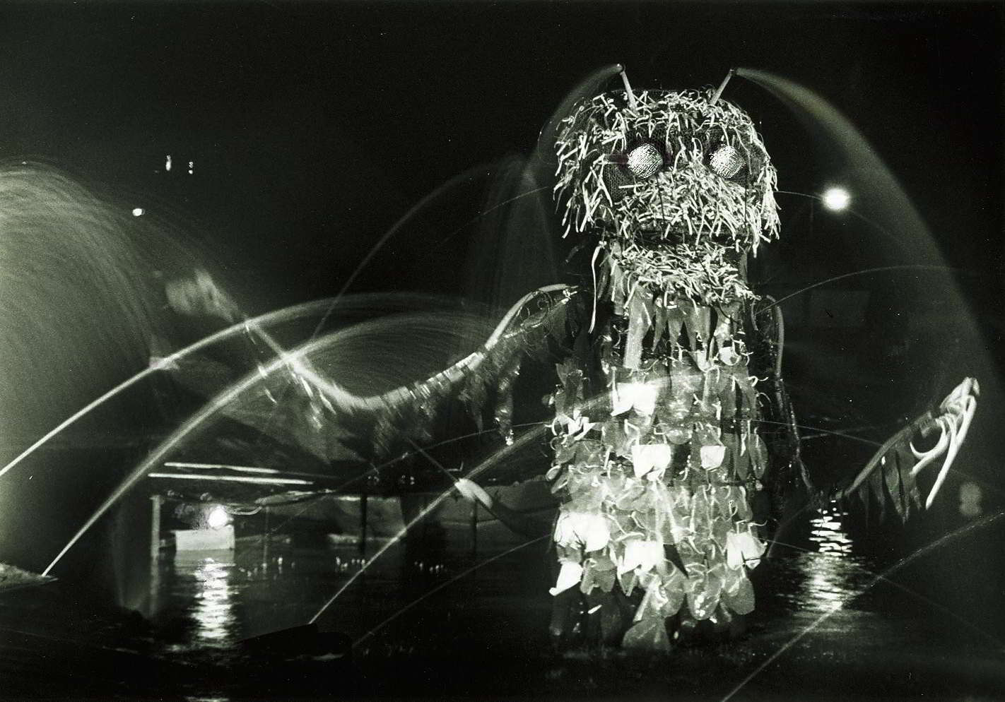 large creature rising from water with water sprays spinning from its body in spot lights