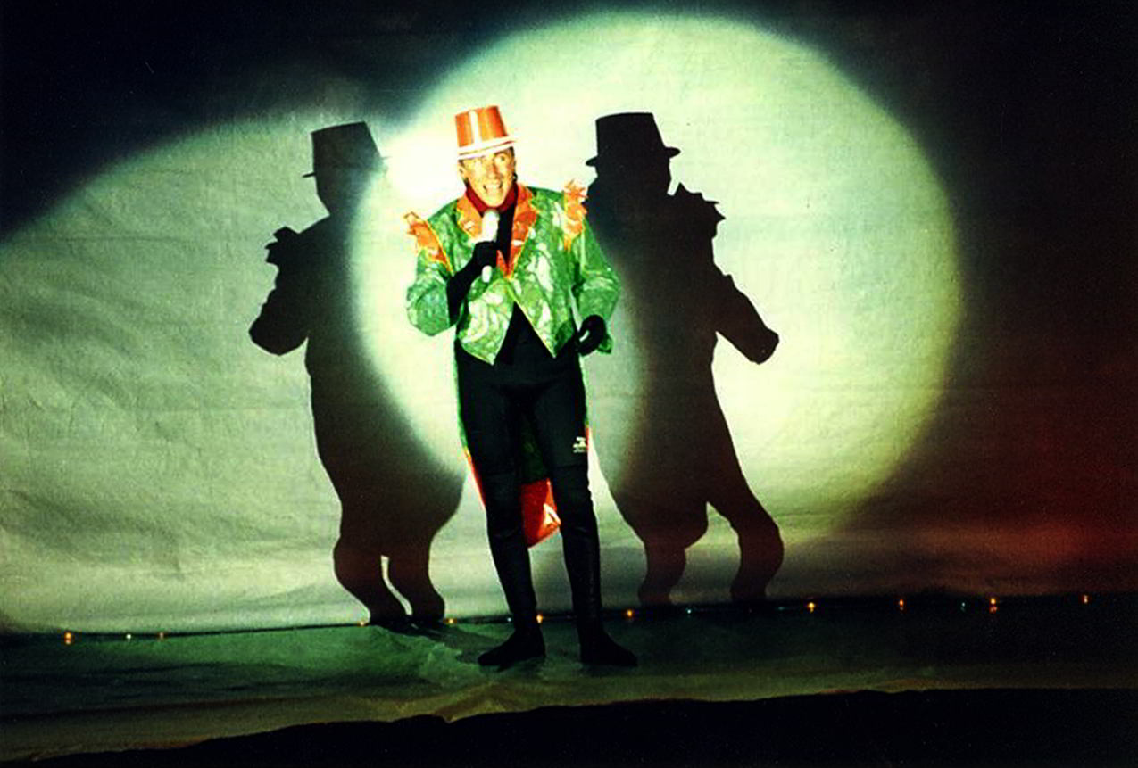 Handspan Theatre Waves of Change Castlemaine Festival figure in orange top hat and green tails in spotlight with double silhouette shadow