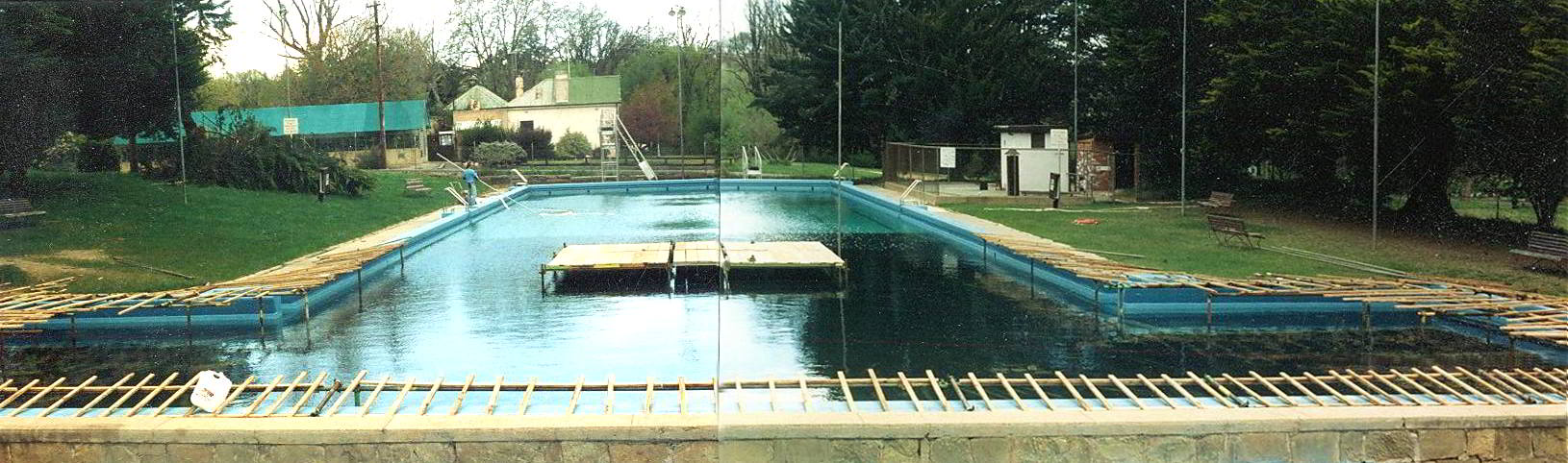 empty swimming pool lined with black plastic with a central scaffolding platform in the centre