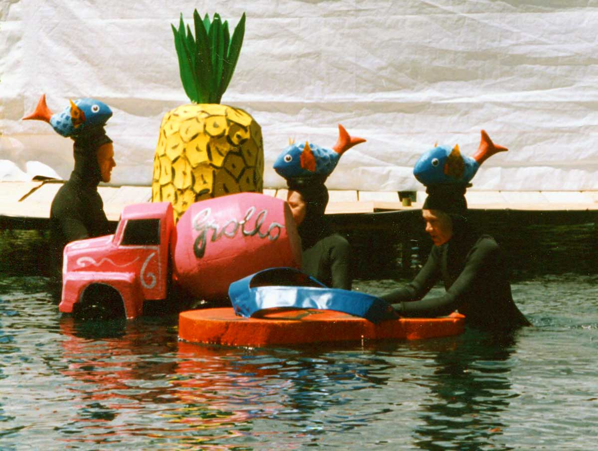 3 puppeteers in wet suits with fish on their heads, operating a large pineapple, thong and cement mixer truck