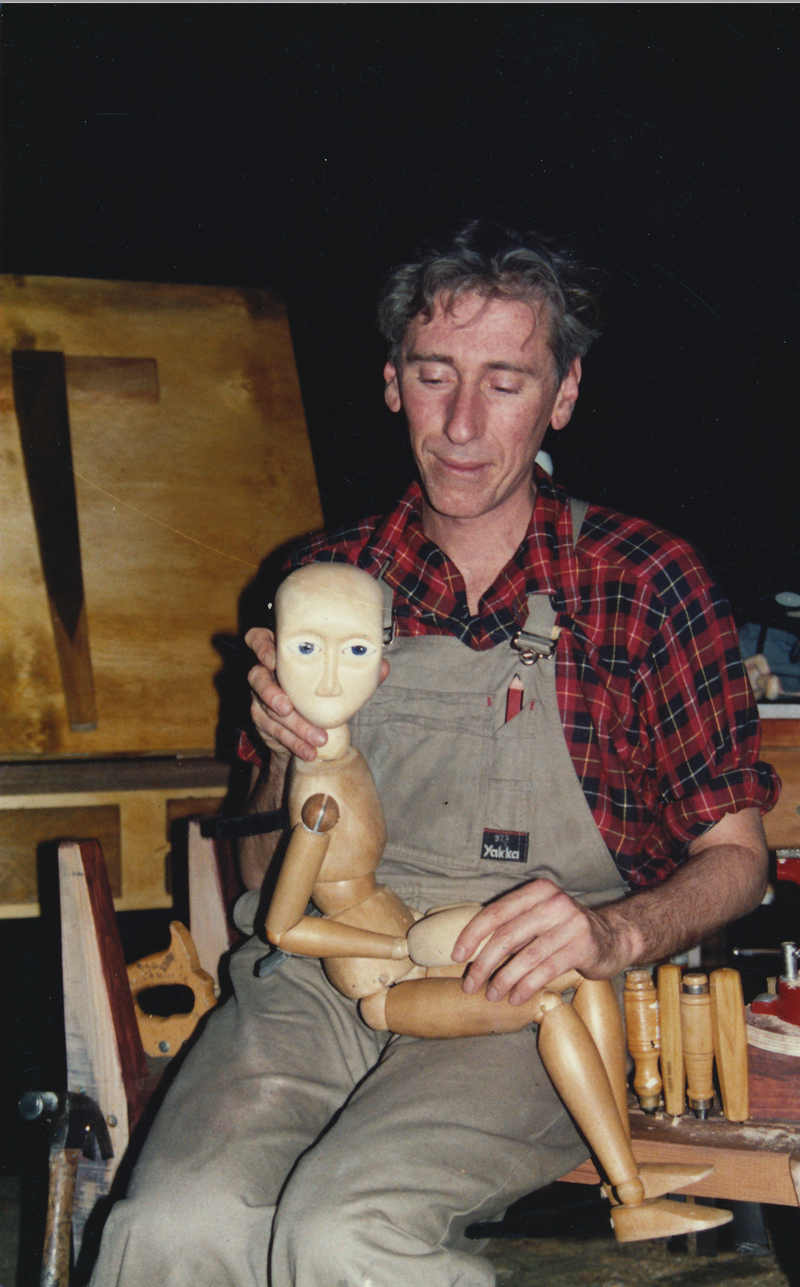 The Wooden Child Handspan Theatre actor sitting, wooden puppet on lap looking at camera