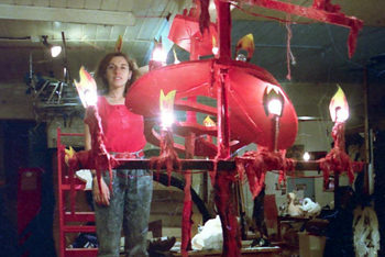 woman stands on workbench beside tall red candelabra