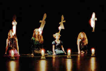 four girls watch as paper dolls, lit from candles, burn away.