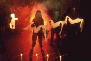black-clad puppeteers carry sleeping girls in smoke and blazing orange light
